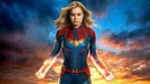 Imagem promocional com Capitã Marvel em seu uniforme tradicional com poderes nos braços a frente de um céu enevoado colorido azul e amarelo. Rankeado como um dos piores filmes do UCM.