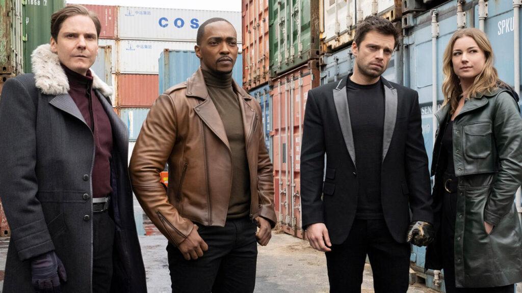 Os personagens Barão Zemo, Sam Wilson, Buck Barnes e Sharon Carter/Mercador do Poder estão encarando algo com diversos contêiners ao redor.